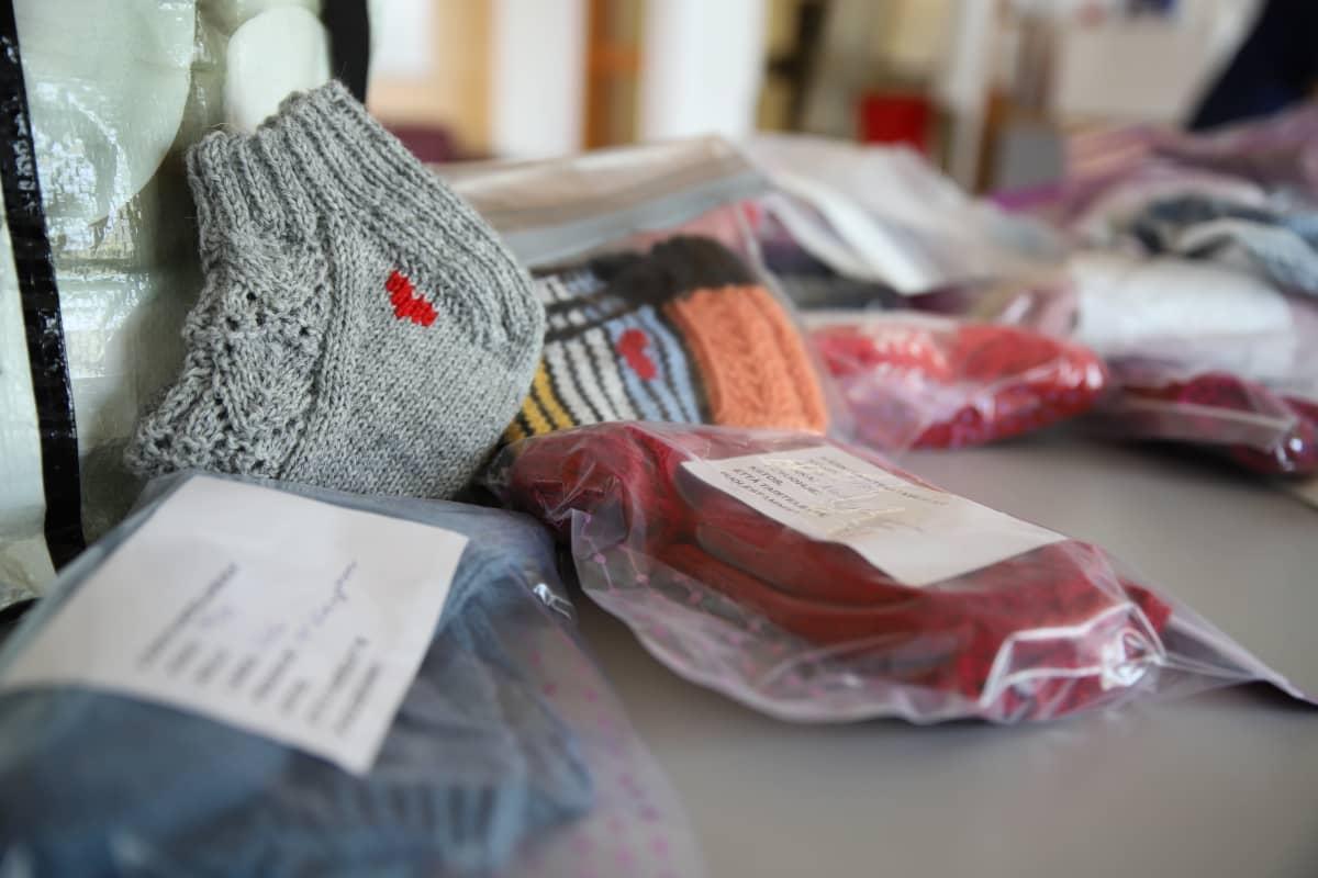 Lahjoitettuja villasukkia, joihin on silmukoitu pieni punainen sydän.