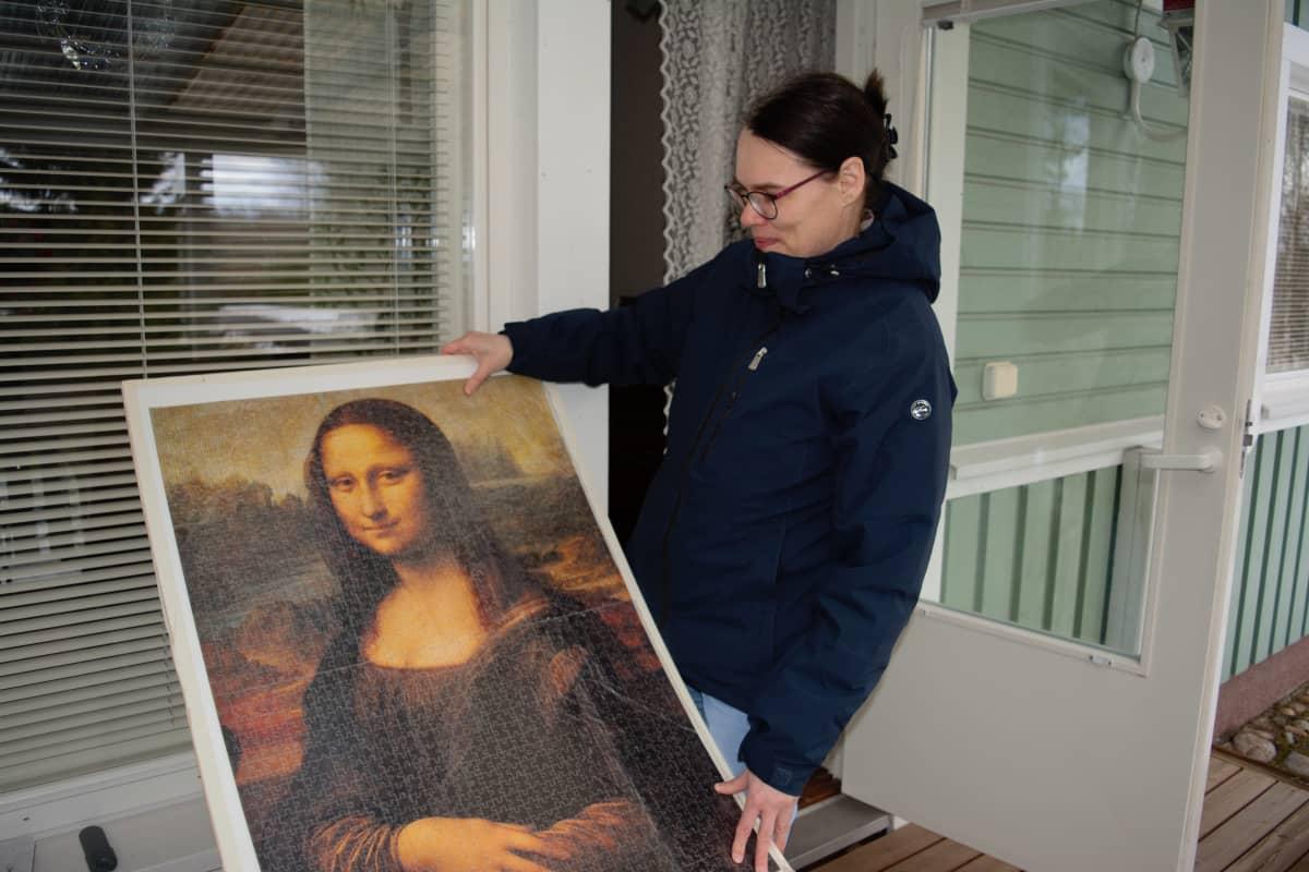 Kirsi Saari esittelee kokoamaansa Mona Lisaa esittävää isoa palapeliä