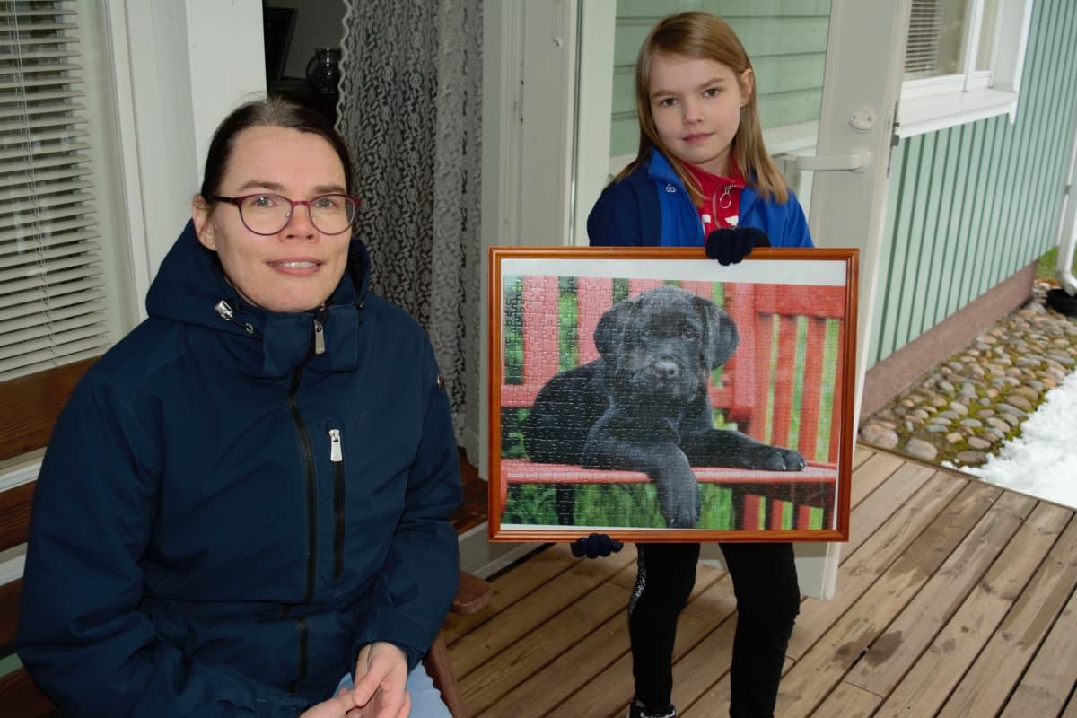 Kirsi ja Aino Saari näyttävät koira-aiheista palpeliä, joka on kehyksissä