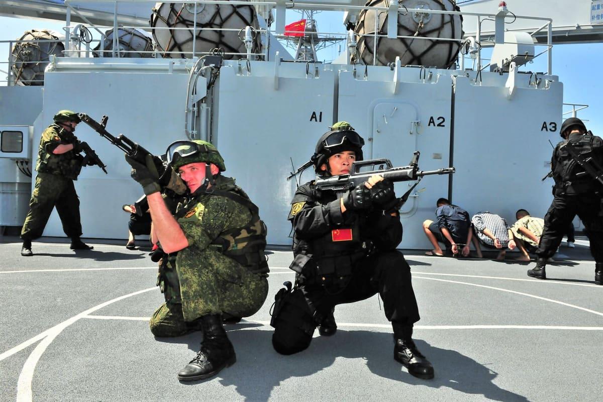 Kaksi sotilasta, venäläinen ja kiinalainen on polviasennossa aluksen kannella ja tähtää aseillaan jonnekin kuvaajan taakse. Taustalla näkyy sotilaita, jotka ovat harjoituksessa pidättämässä aluksen kannella olevia siviiliasuisia miehiä.