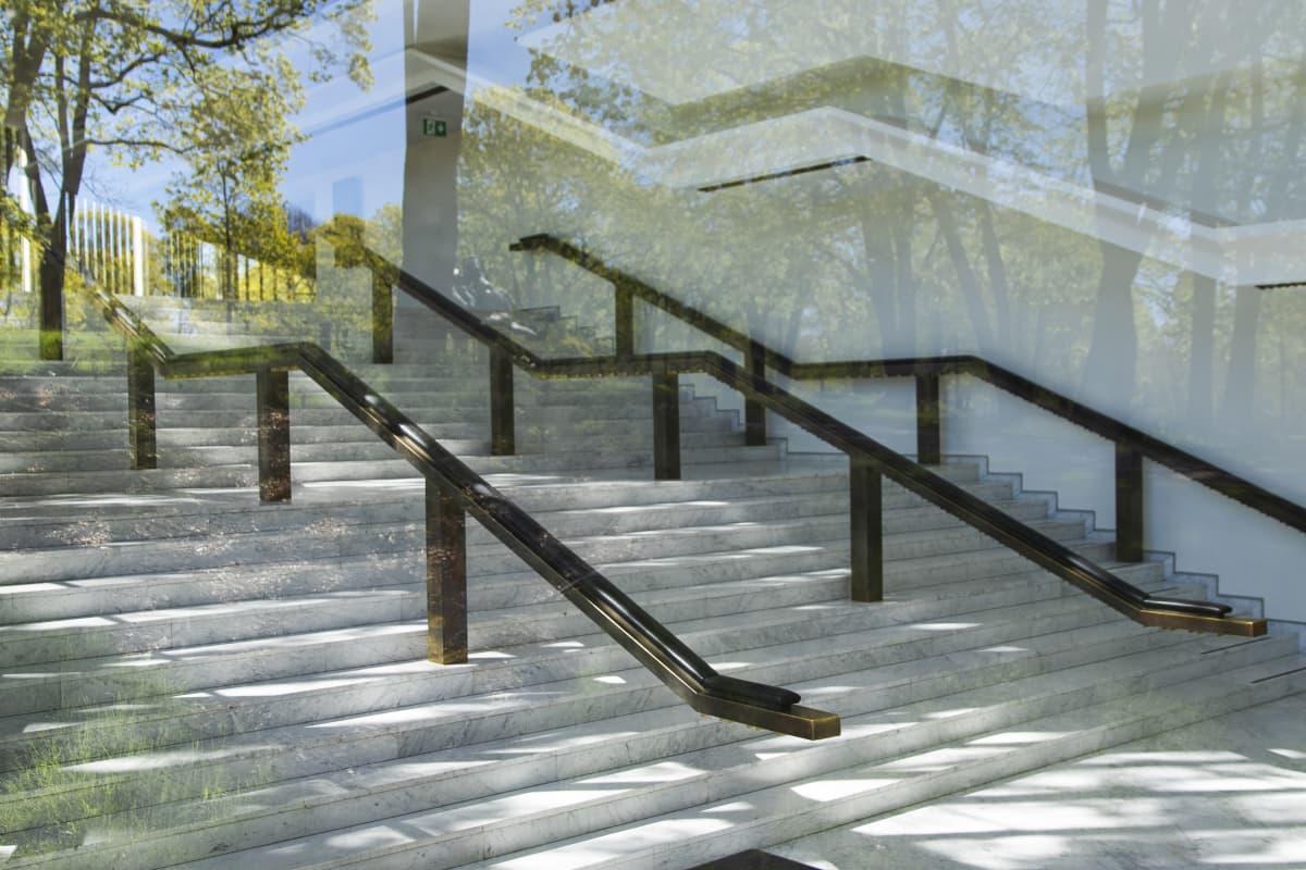 Helsingin kaupunginteatterin aulan portaikko. Kuvattu ikkunan läpi, pihan puut heijastuvat ikkunasta.