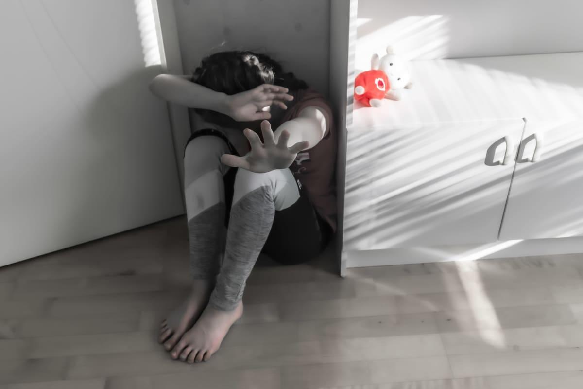 Dramatisoitu kuva, jossa lapsi istuu nurkassa suojaten kädellä päätään ja torjuen uhkaa toisella.