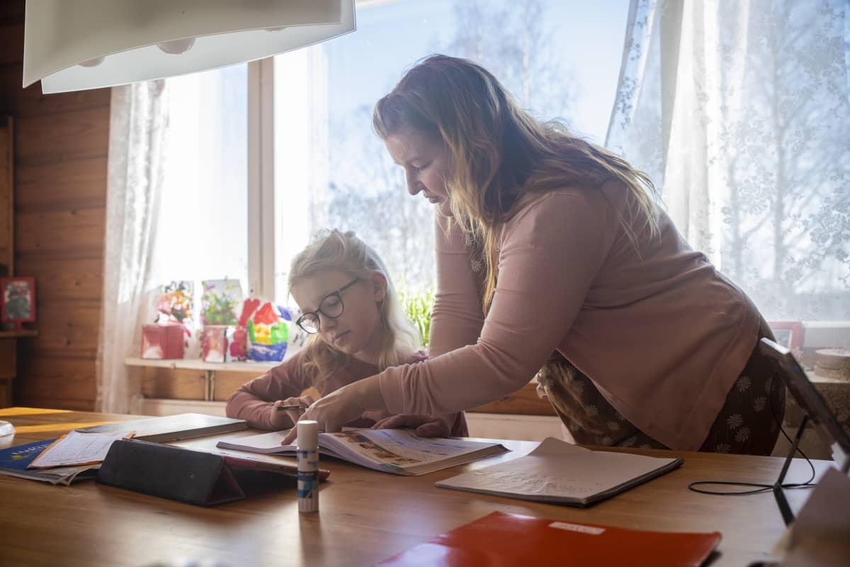 Riina Pirskanen auttaa lastansa Kerttua koulutehtävissä