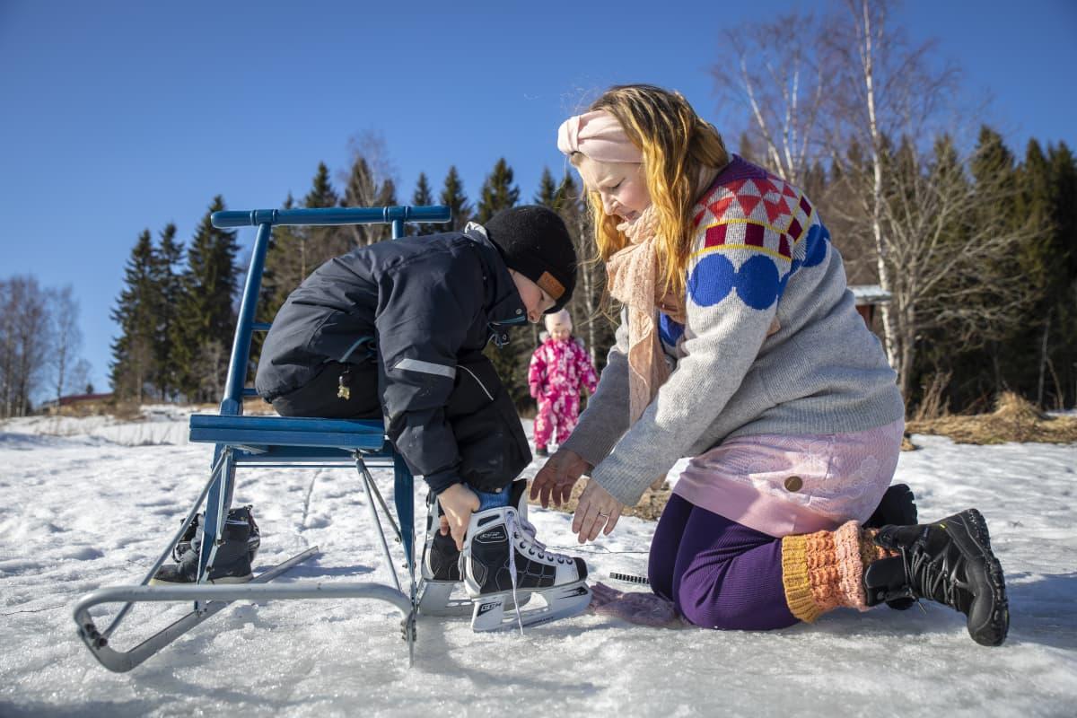 Riina Pirskanen auttaa hänen lapsellensa, Jaakolle luistimia jalkaan