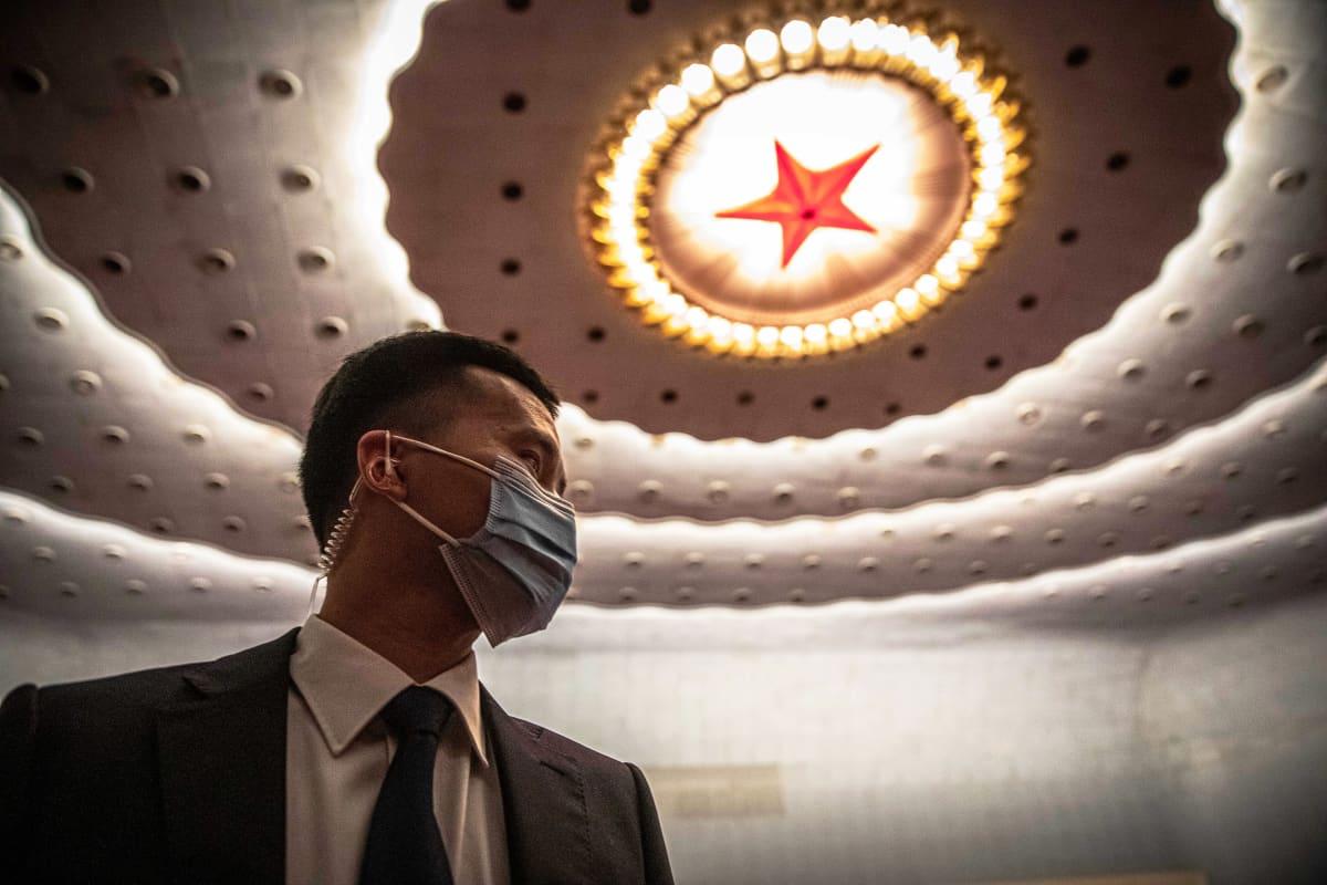 Turvallisuusmies seisoo suuressa hallissa. Katossa on suuri punainen tähti.