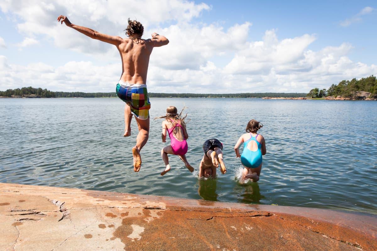 En kille och några barn hoppar i vattnet från en klippa.