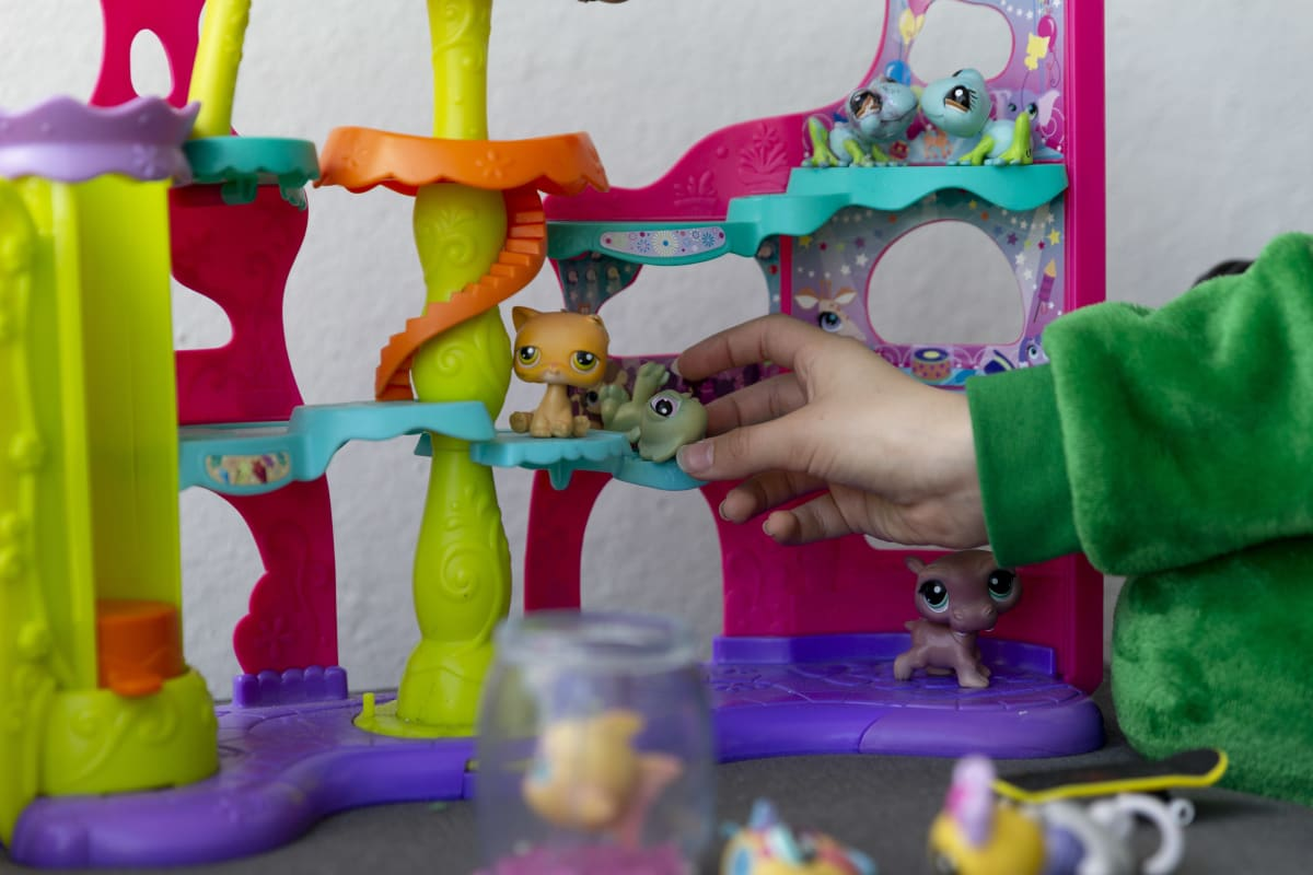 Lapsi leikkii Littlest Petshop leluilla.