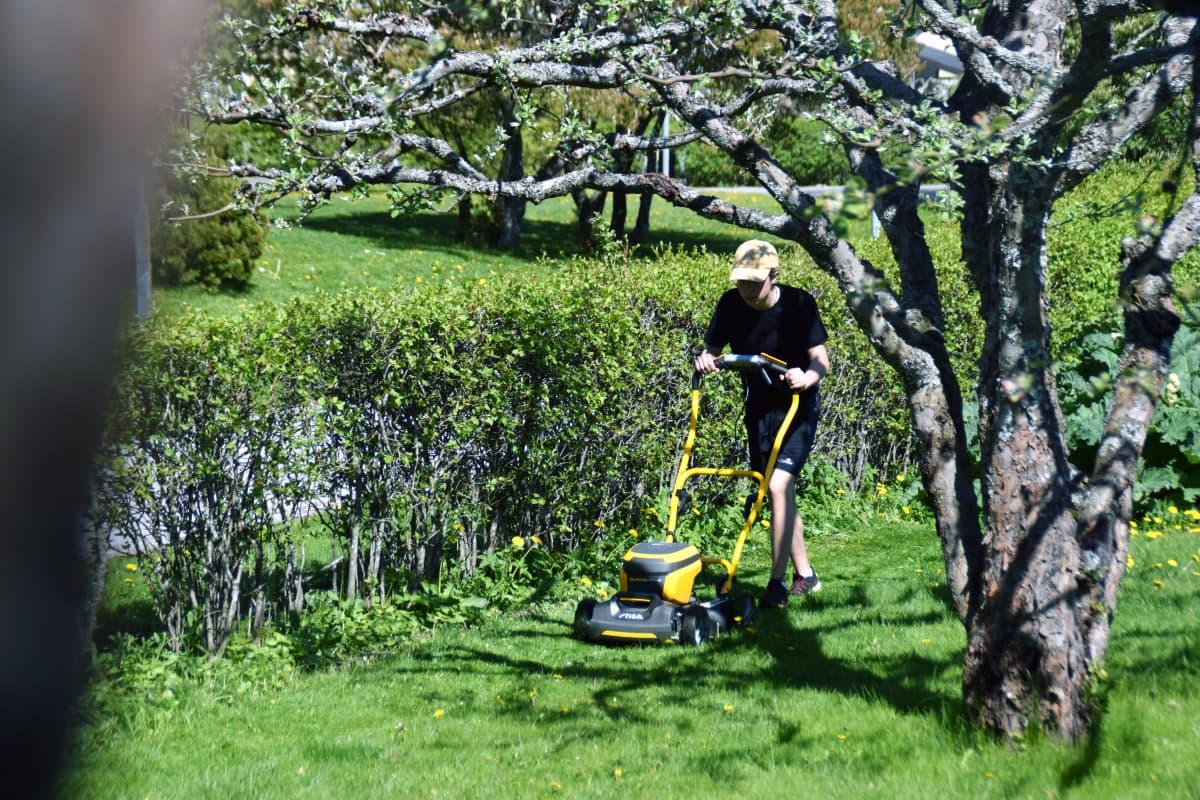 Nuori leikkaa nurmikkoa ruohonleikkurilla.