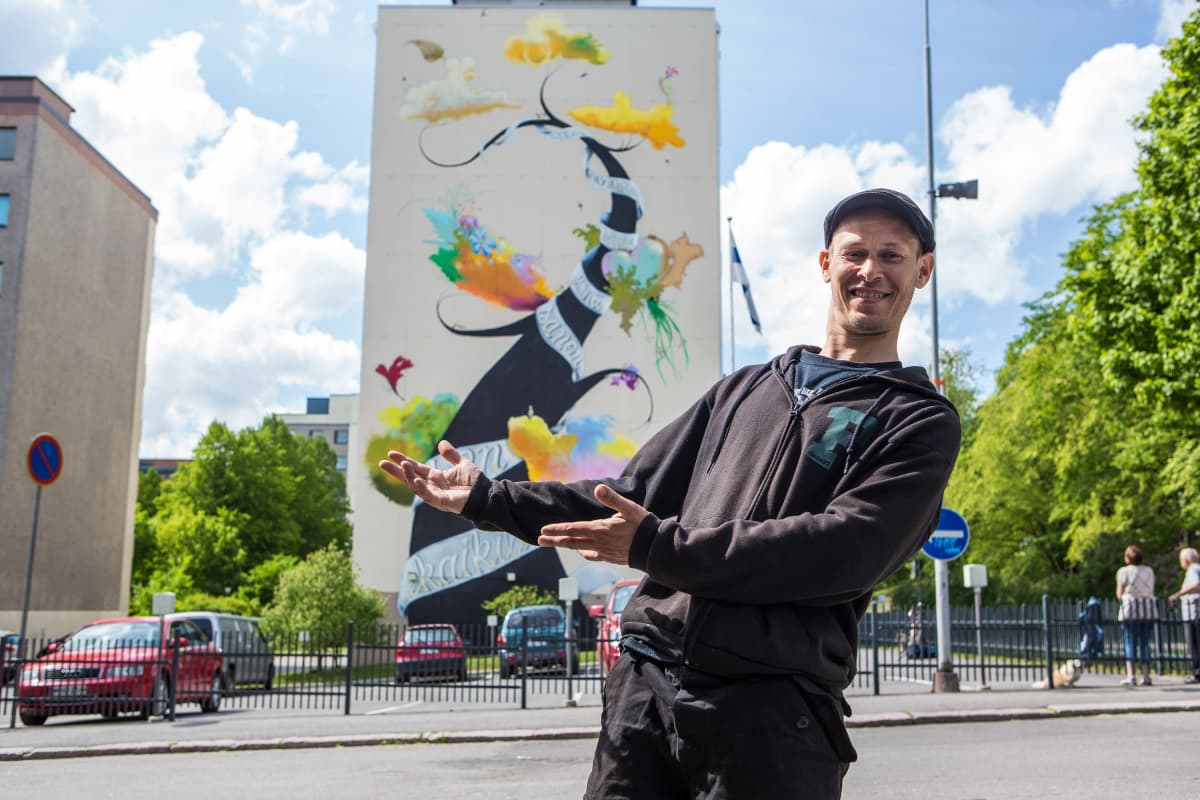 Taiteiija Teemu Mäenpää esittelee Runopuu-muraaliteosta Tammelassa Tampereella.