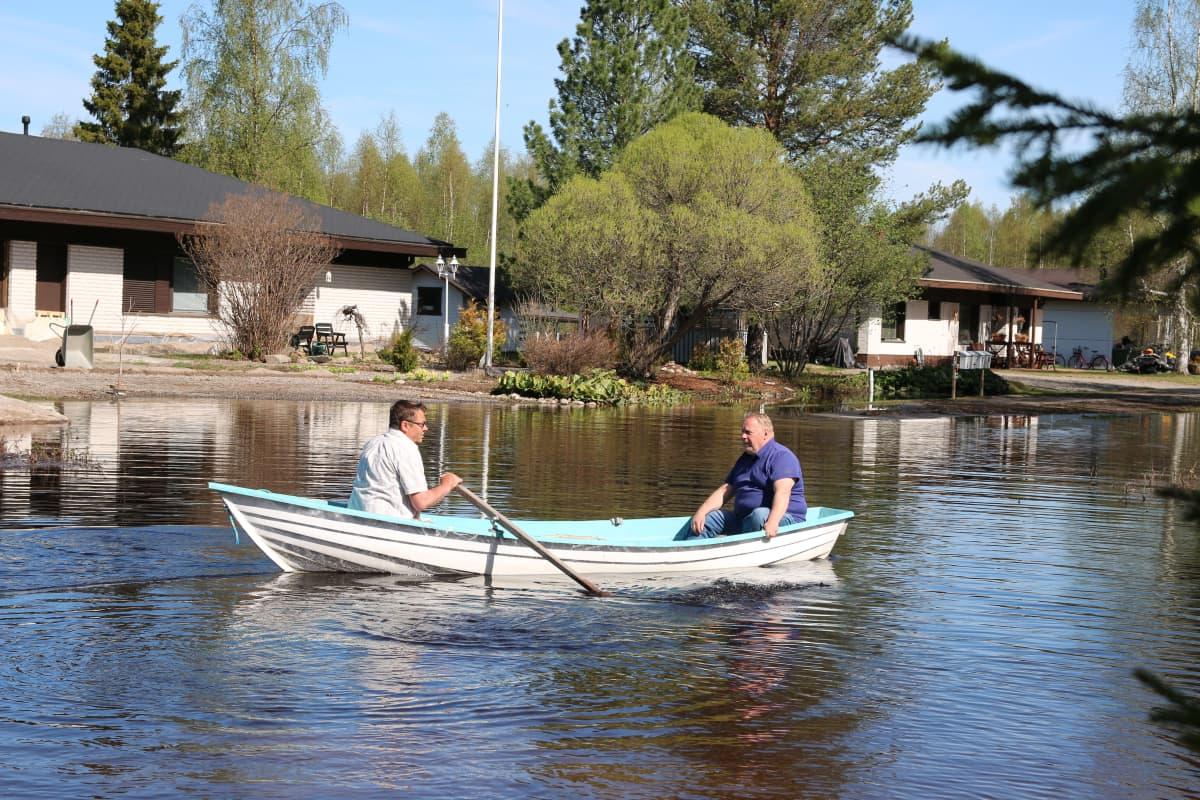 Jussi Uutela ja Heimo Flinck soutavat tulvaveden täyttämällä kadulla