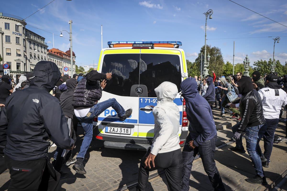Joukko huppupäisiä ihmisiä poliisiauton ympärillä. Yksi potkii autoa.