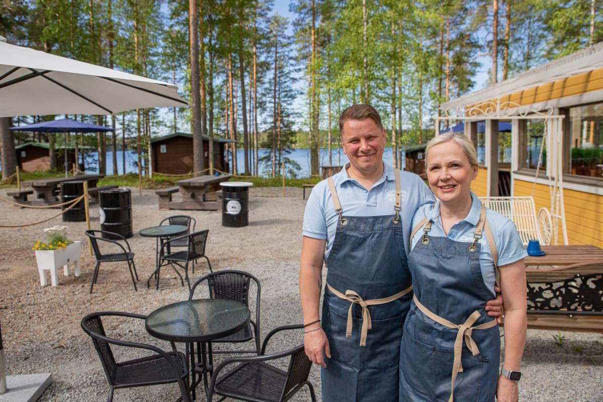 Jukka Vuorela ja Minna Luoma-aho poseeraavat leirintäalueen pihalla.