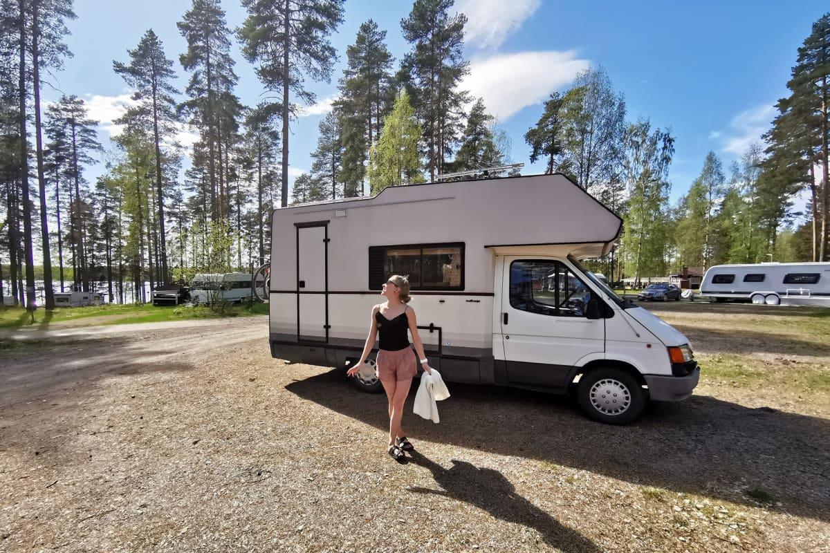 Anni Vilkki poseeraa asuntoautonsa edessä.