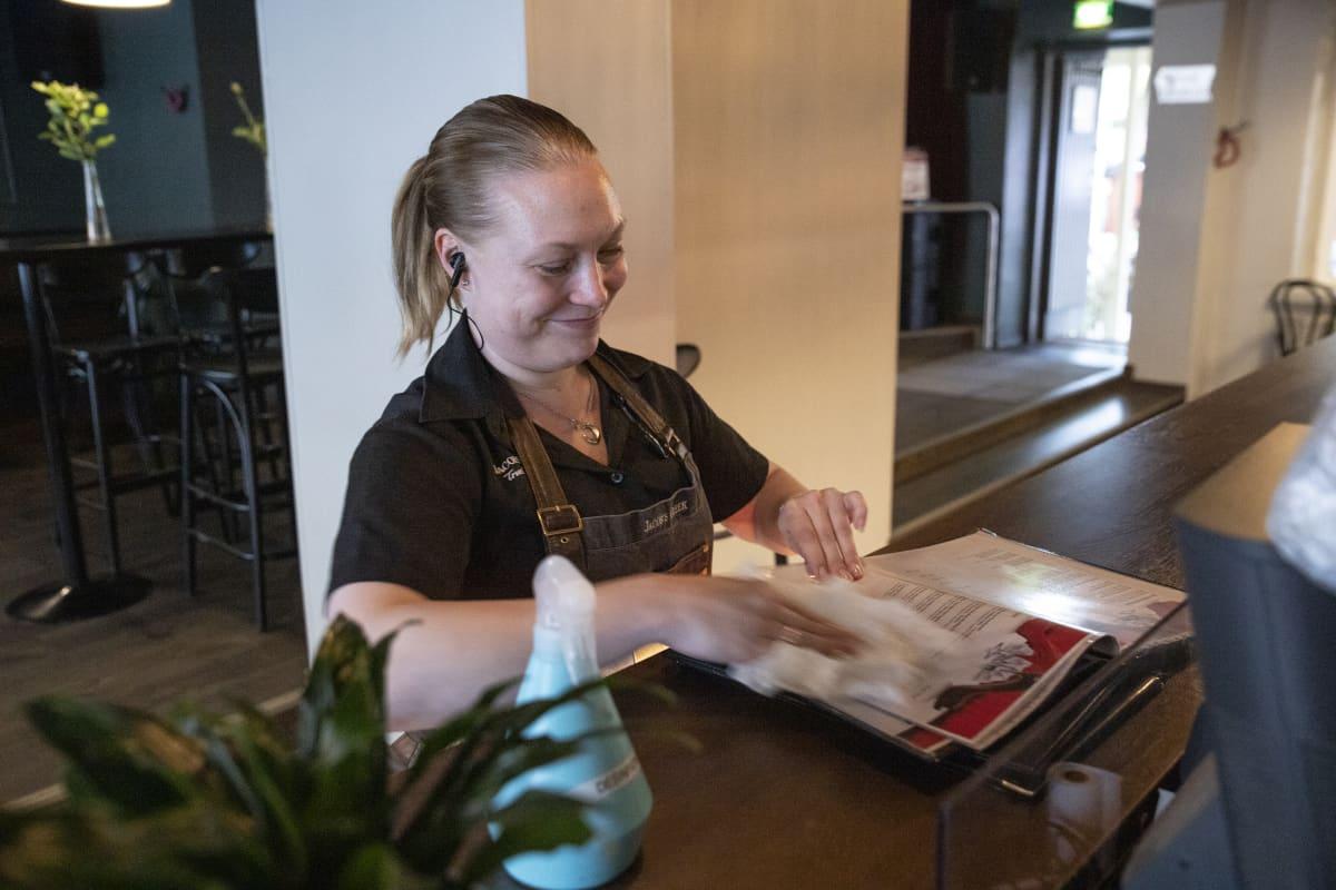tarjoilija Minna laukkanen desinfioi  ruokalistoja asiakkaiden käytön jälkeen ravintola Kummisdässä Kuopiossa