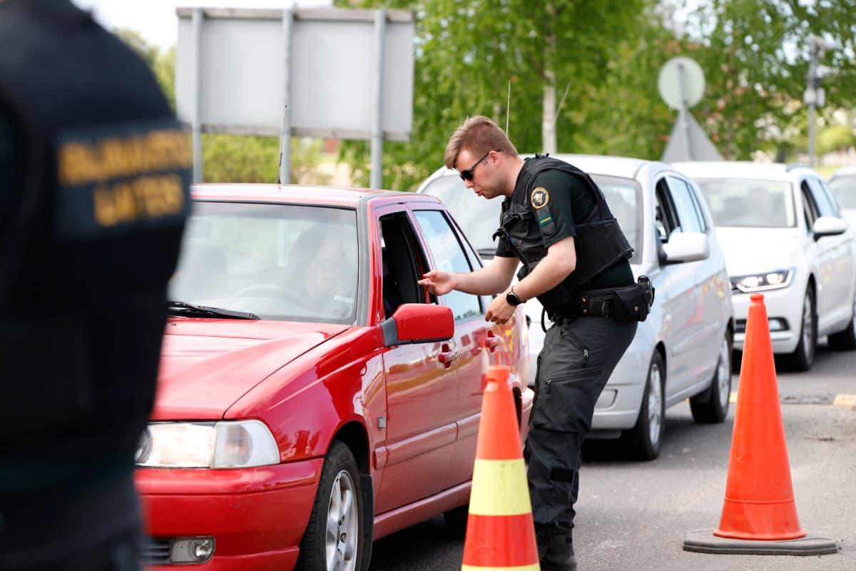 Rajavartija jututtamassa Torniossa rajan yli pyrkiviä autoilijoita.