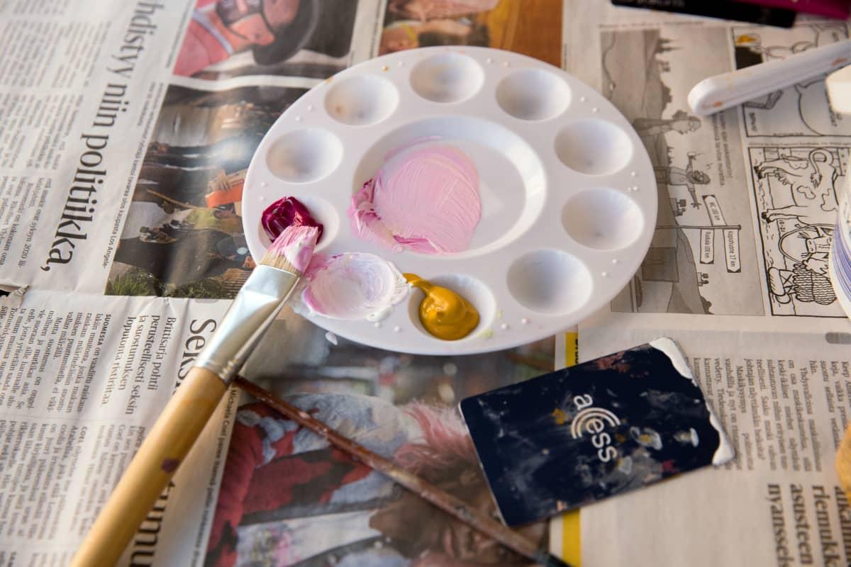 Taidemaalarin tarvikkeita pöydällä.
