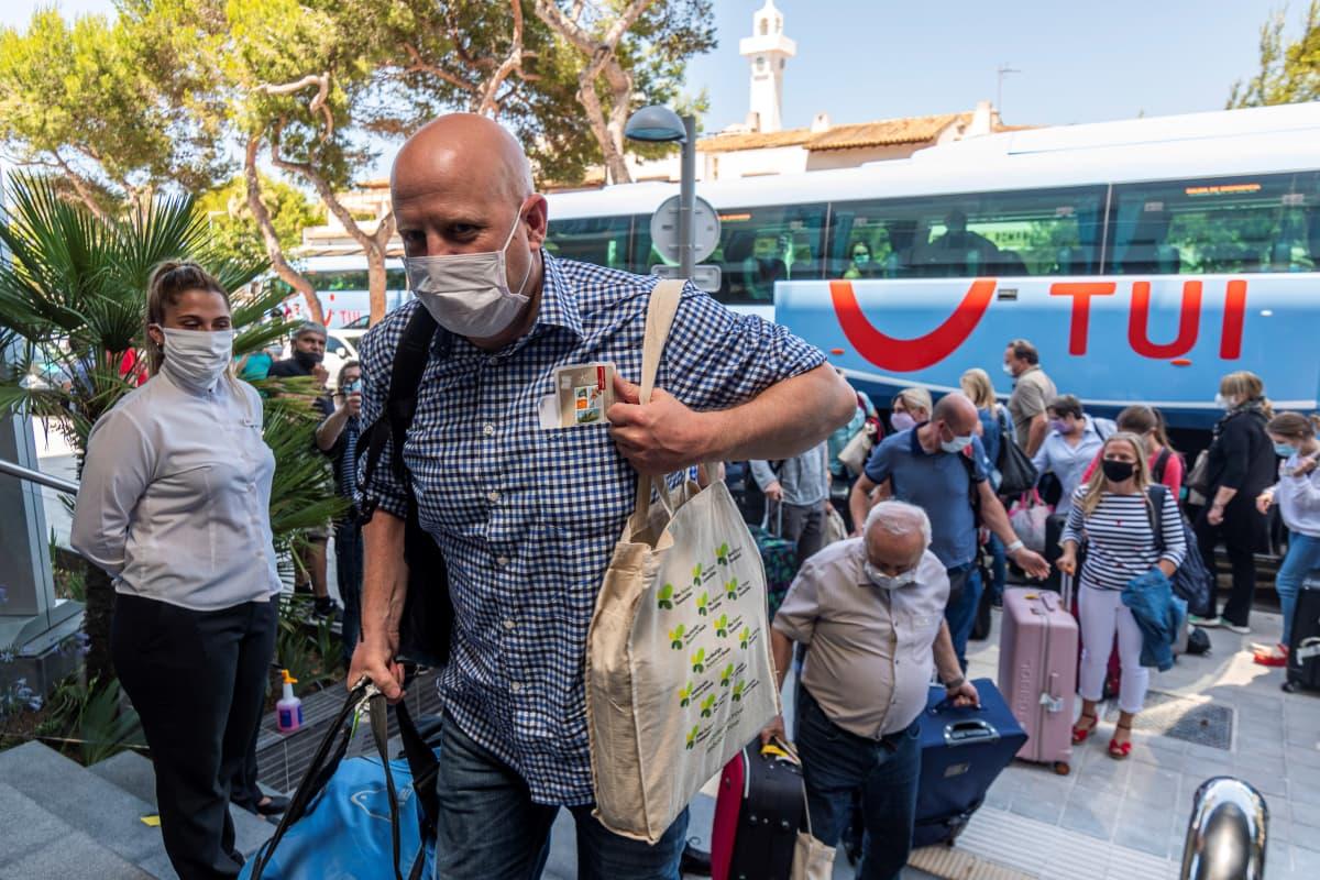 Turistit purkautuvat matkatoimiston bussista maskit kasvoillaan.