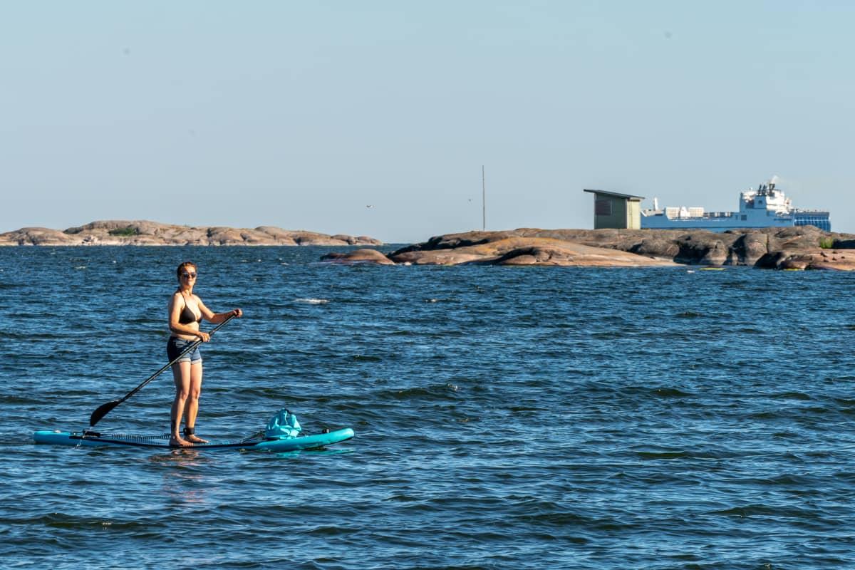 Nainen suppailee merellä.