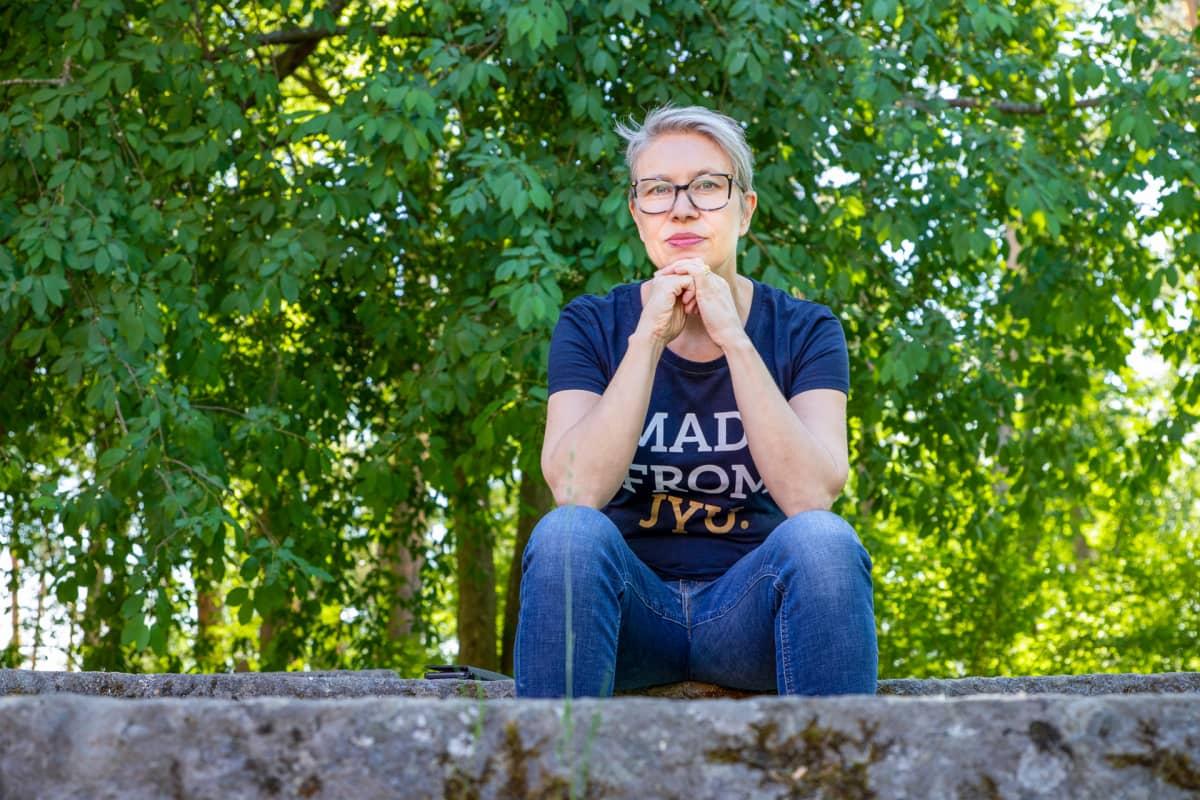 Varpu Marjomäki istuu kivestä tehdyllä istuimella.