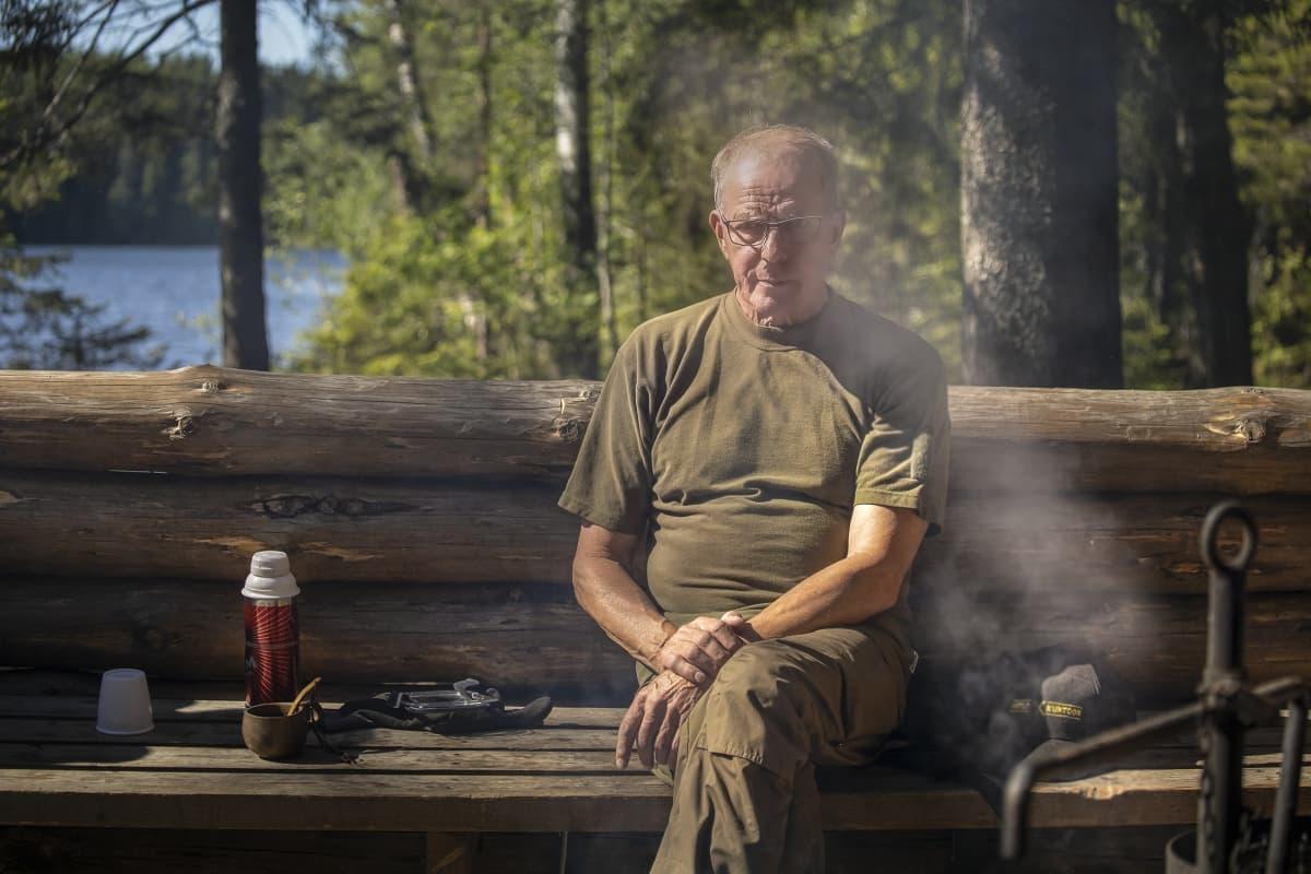 Paavo Seppänen istuu nuotion savussa.
