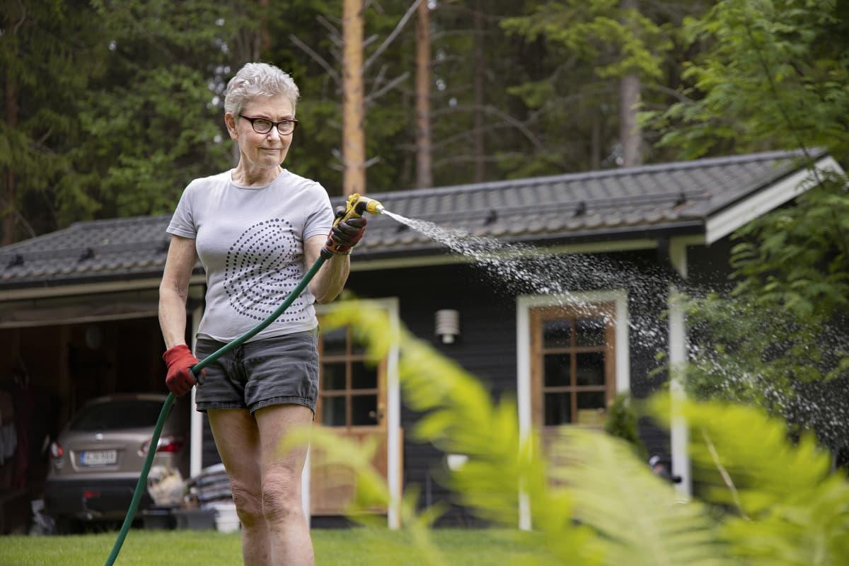 Pirjo-Leena Pitkänen kastelee kukkia.