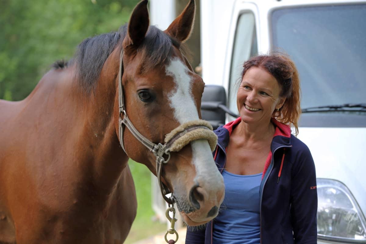 Melina Holmberg hevosensa vieressä.