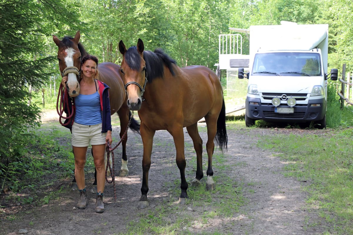 Melina Holmberg hevostensa vieressä takanaan hevoskuljetusauto..