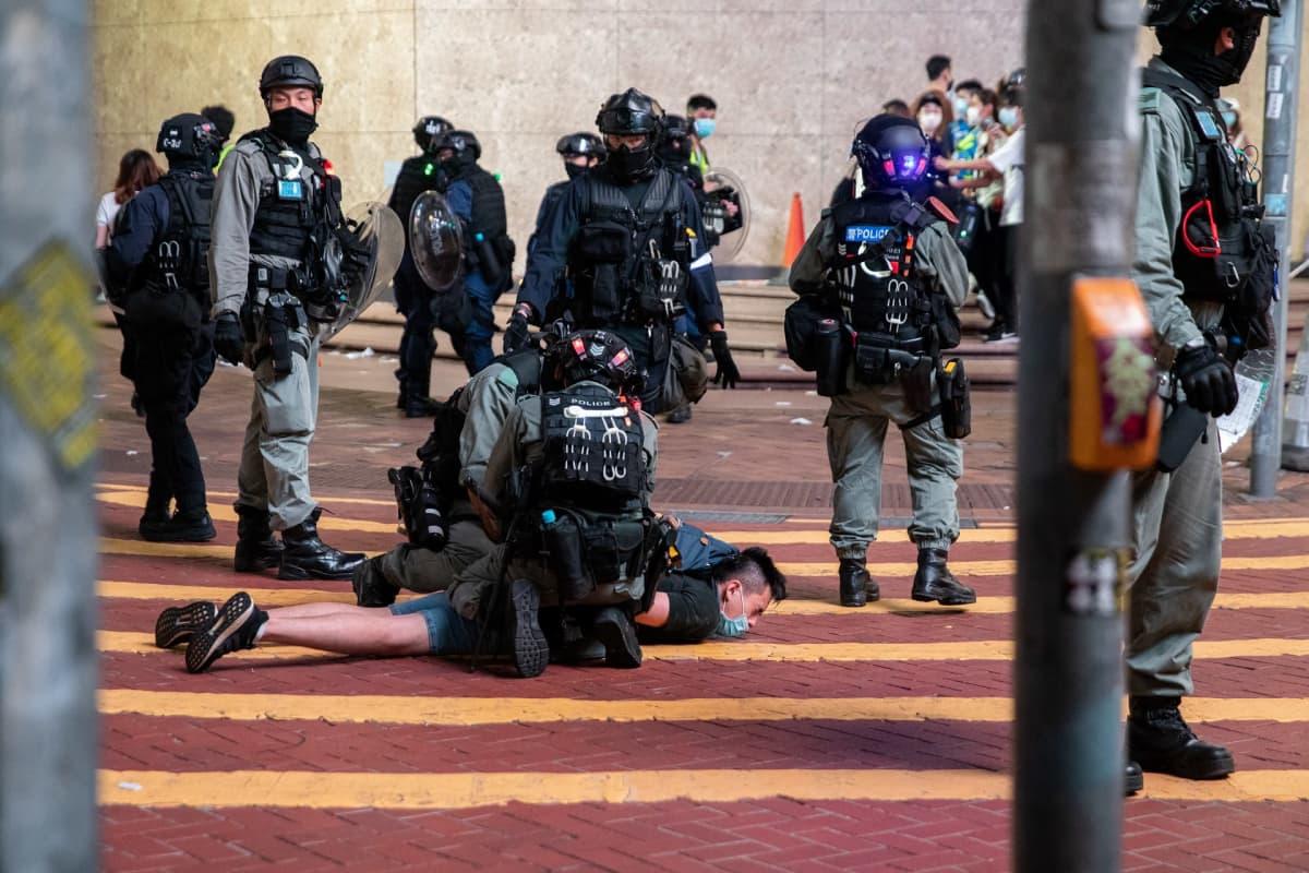 Mies on maassa poliiseja ympärillään.