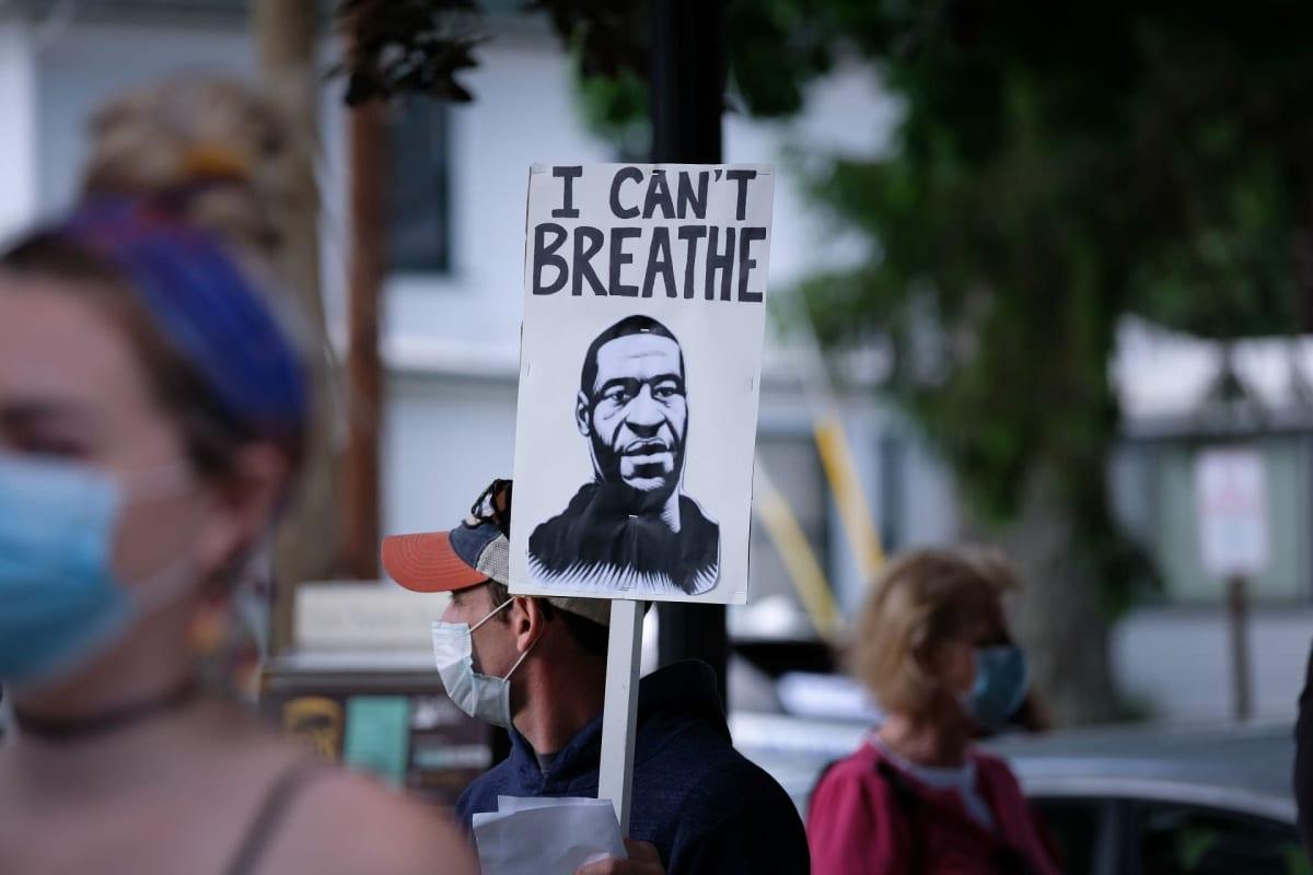 """Mielenosoittaja kantaa julistetta, jossa on piirros George Floydista ja sanat """"I can't breathe"""" (en voi hengittää)"""