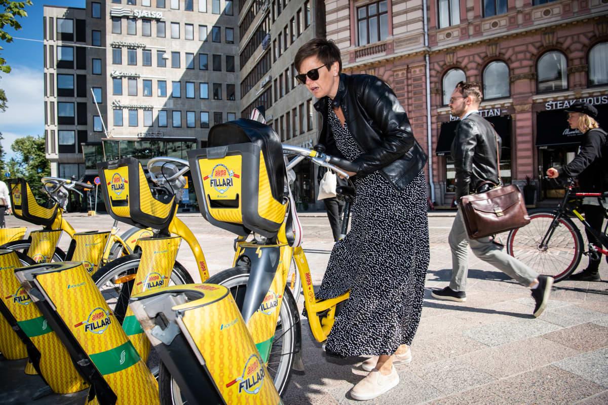 Nainen palauttamassa kaupunkipyörää Helsingissä.