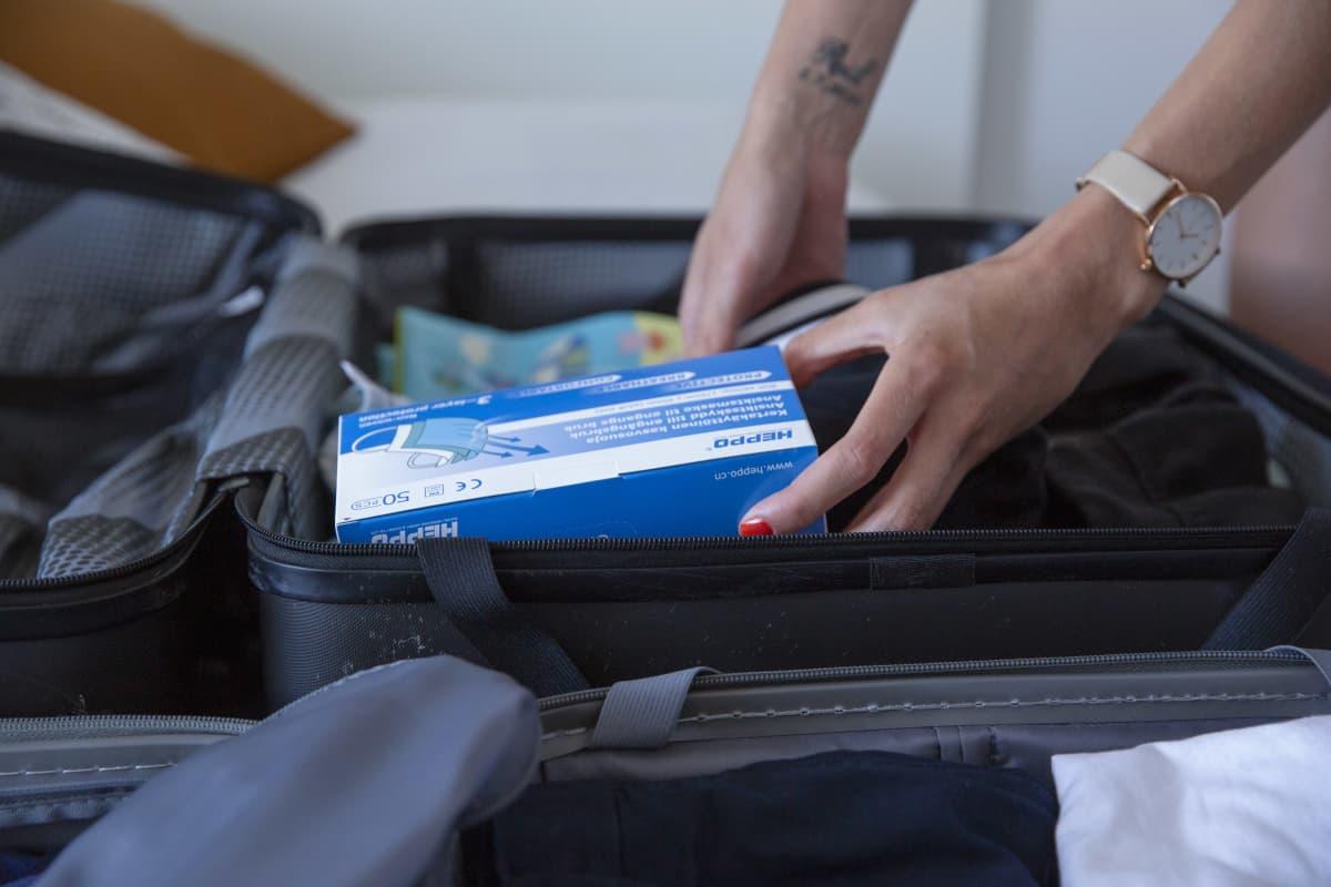 Suojamaskeja pakataan matkailaukkuun.