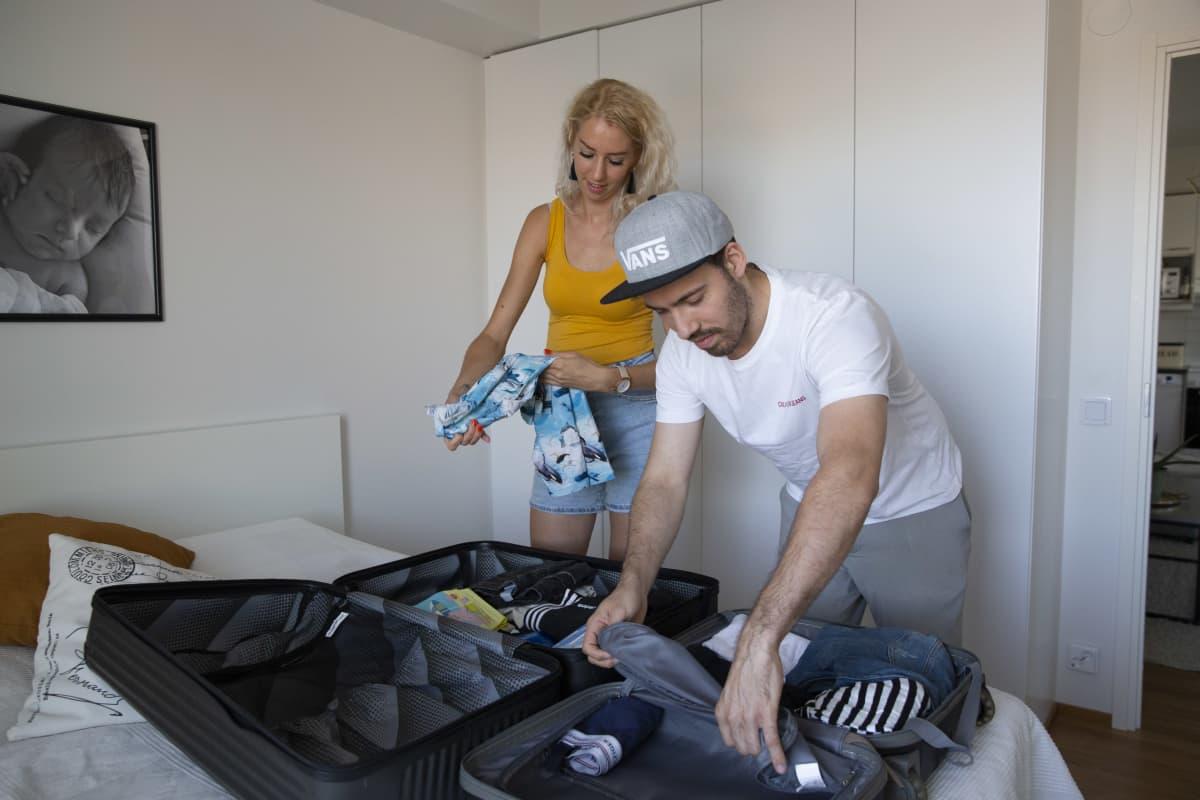 Pariskunta pakkaamassa matkalaukkuja.