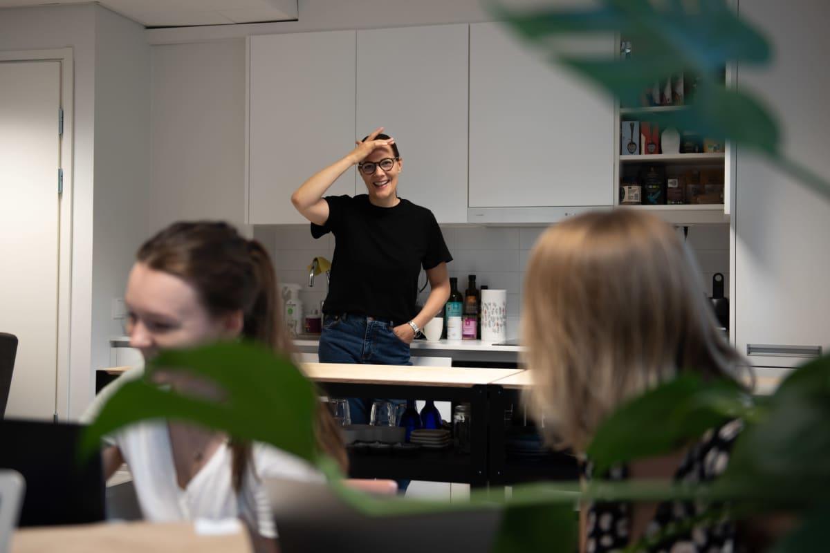 Outi Ellilä keittää kahvia toimiston keittiössä, etualalla kesätyöntekijät valmistautuvat kokoukseen.