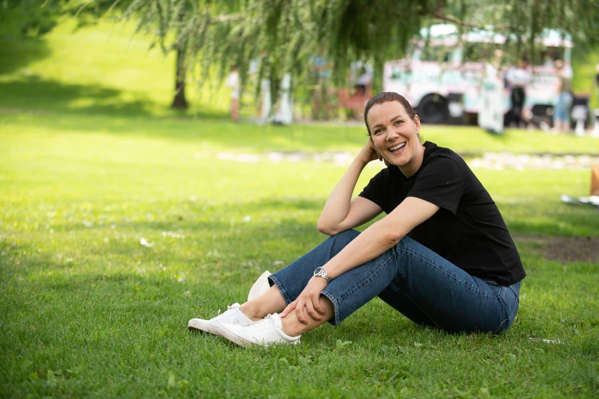 Outi Ellilä istuu puistossa.
