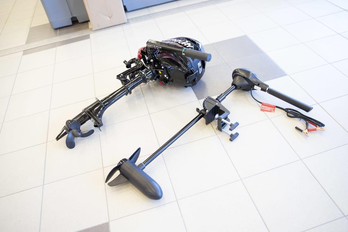 Perinteinen perämoottori ja sähköperämoottori lattialla.