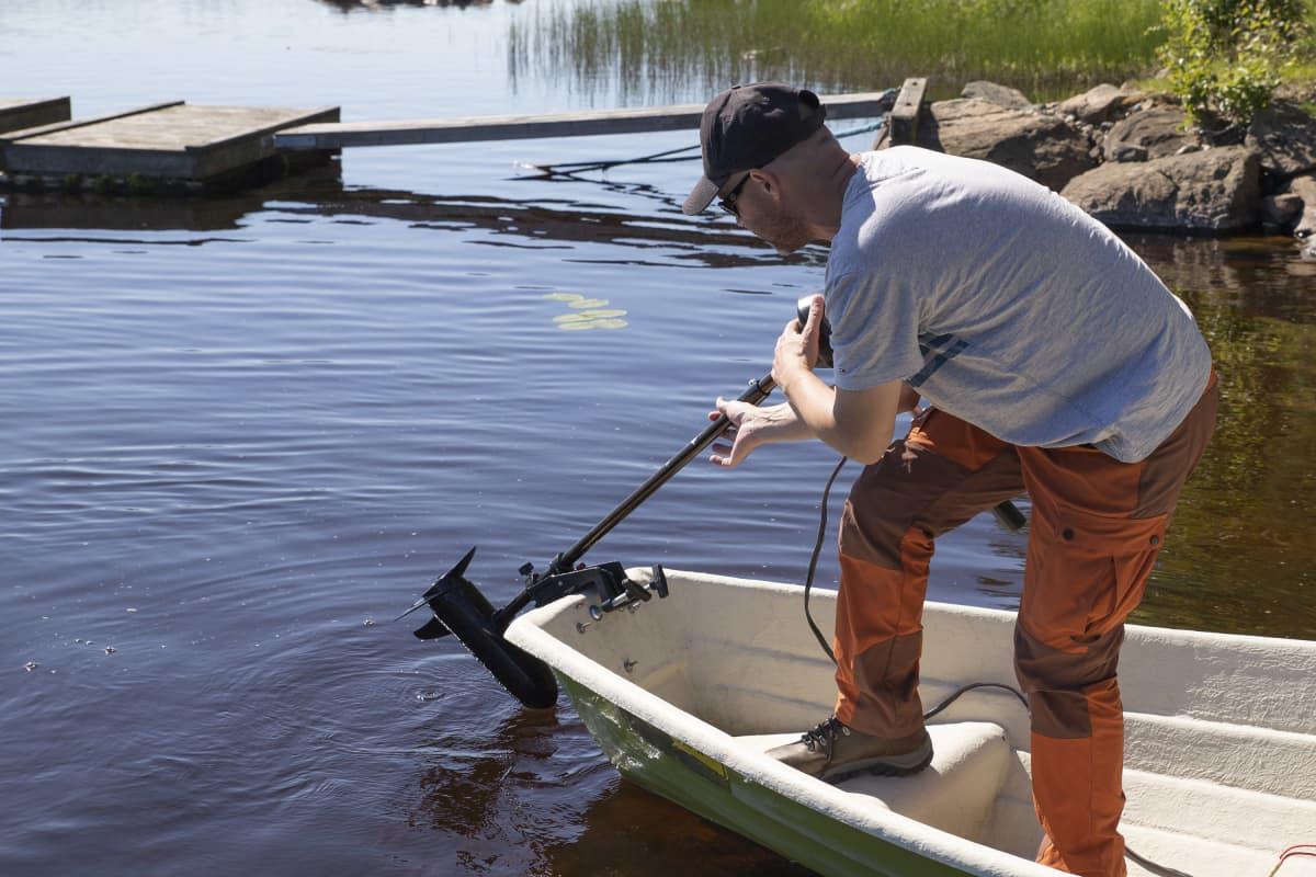 Janne Kokkonen irrottaa sähköperämoottoria veneestä.