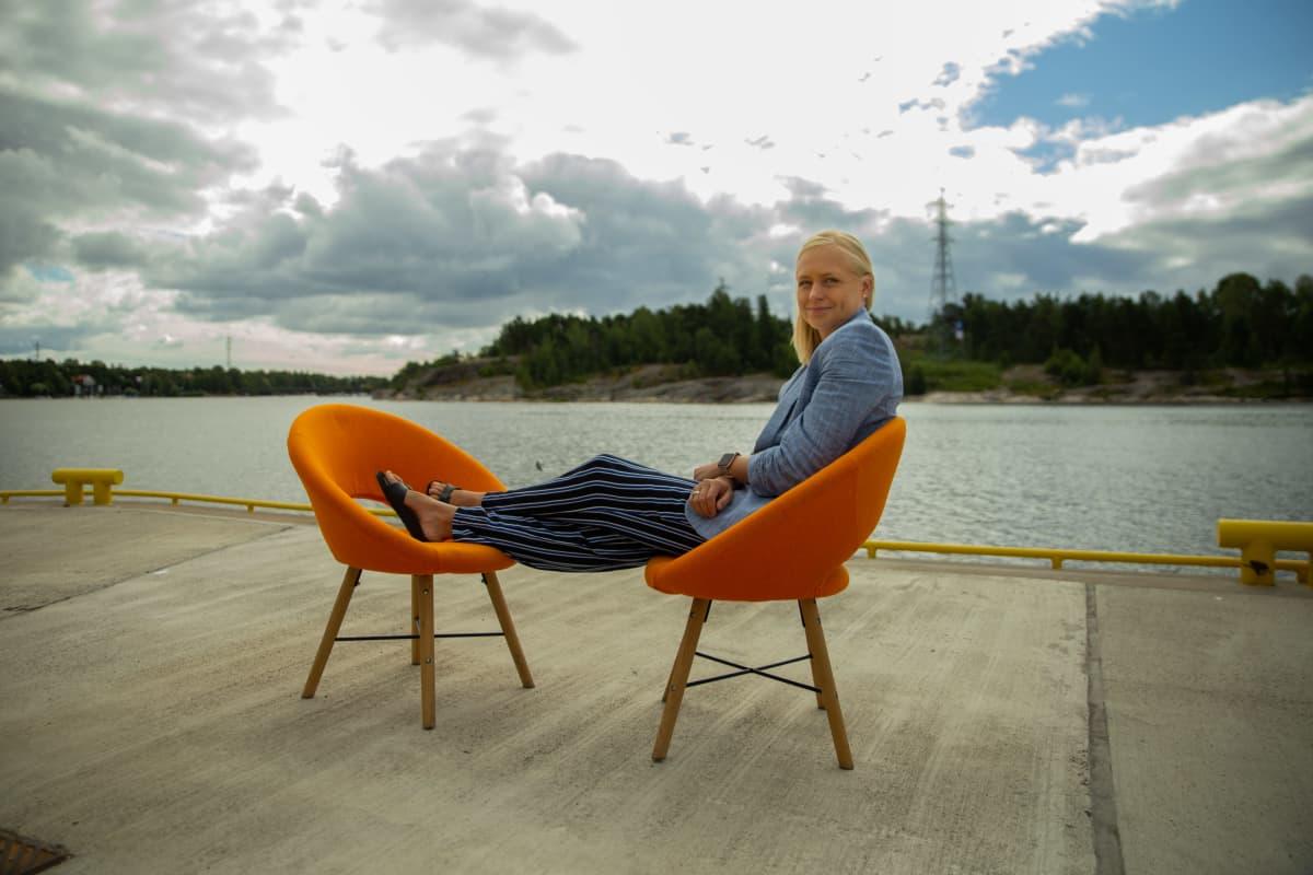 Elina Lepomäki istuu 8 minuuttia -ohjelman oranssilla tuolilla laiturilla Helsingin Kalasatamassa
