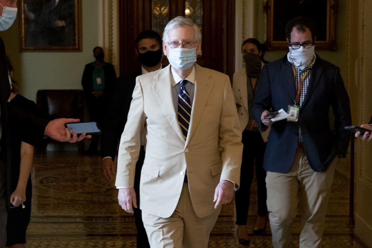Vaaleaan pukuun pukeutunut senaatin republikaanien johtaja Mitch McConnel kävelee toimittajien keskellä Yhdysvaltain kongessissa.