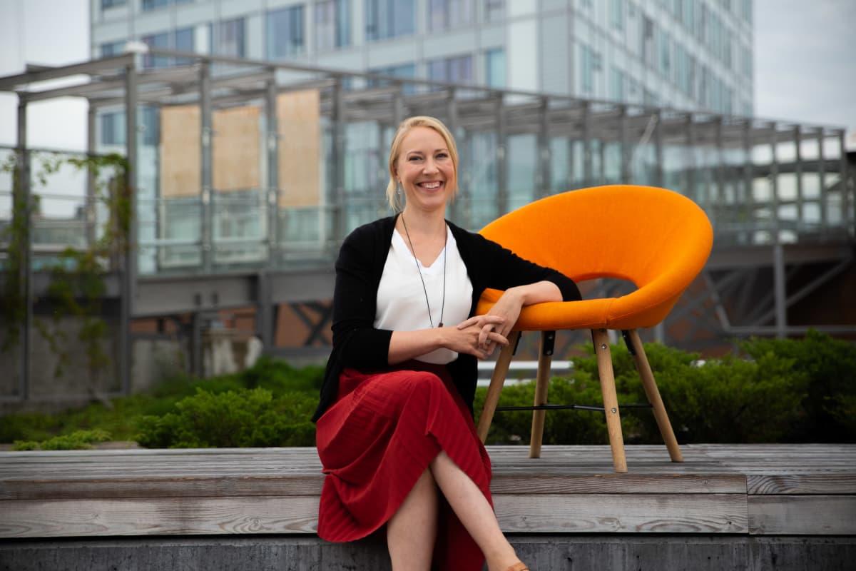 Mona Moisala istuu 8 minuuttia -ohjelman oranssin tuolin vieressä penkillä ulkona kaupunkimaisemassa.