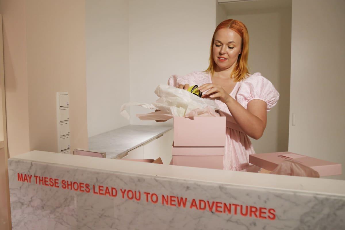 Kenkäsuunnittelija Minna Parikka availee kenkälaatikoita.
