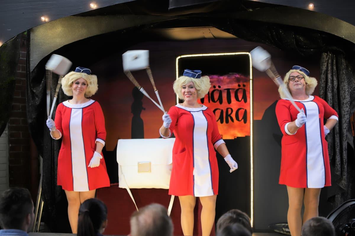 Lentoemännät pyörittävät käsilaukkuja teatteri perikunnan esityksessä.