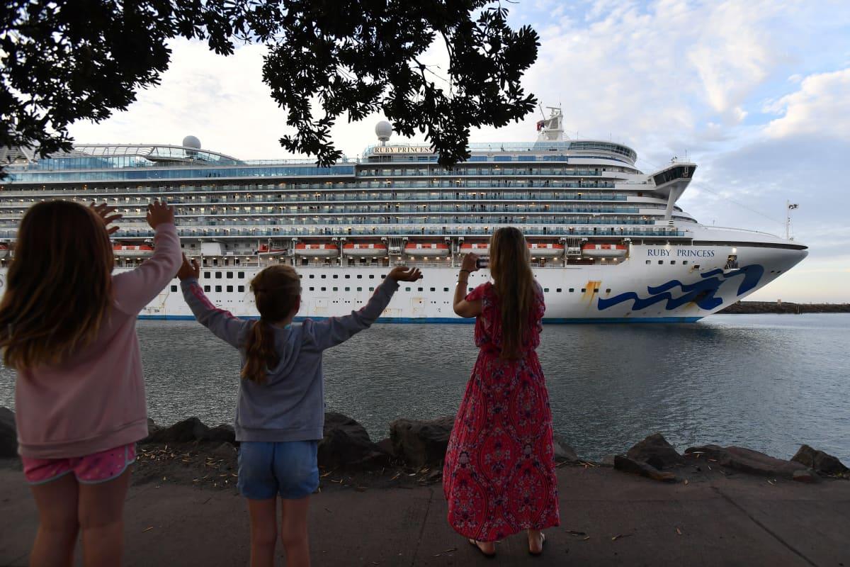 Risteilyalus lähtee satamasta, rannalla lapsia vilkuttamassa