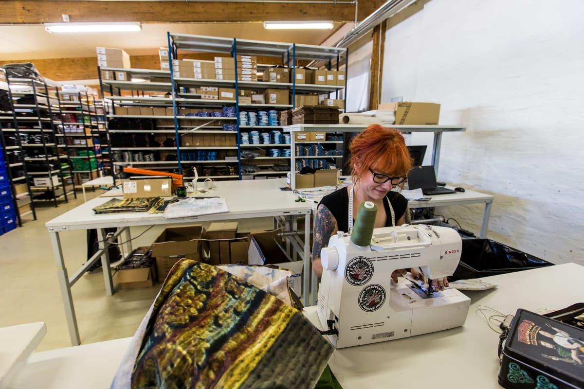 Ninni Huikko ompelee tuotteita vanhasta taustalakanasta Backstage Rock Shopin varastossa Tampereella.