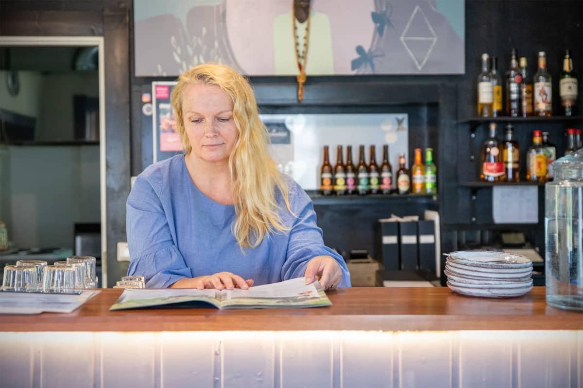 Anne Hakkarainen selaa mainoslehtistä tiskin takana.