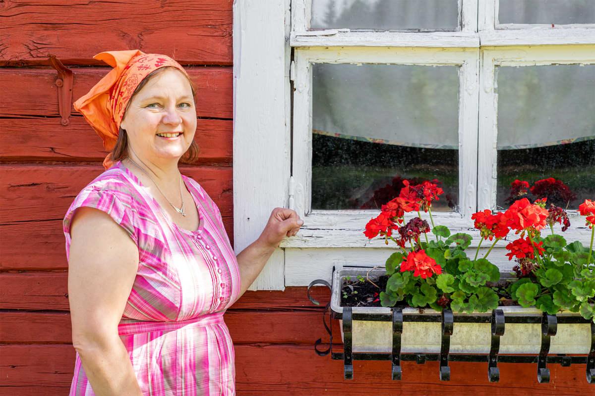 Anne Kalmari poseeraa saunamökin edessä.