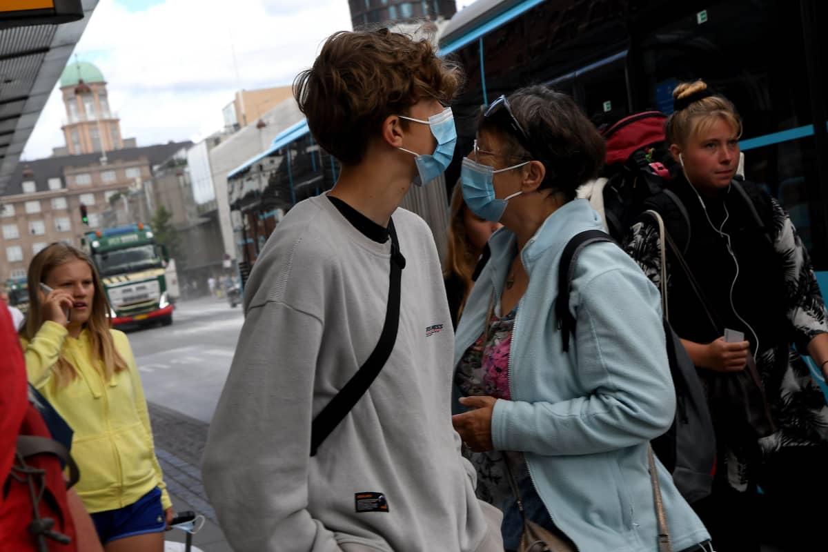Ihmisiä kadulla maskeilla ja ilman