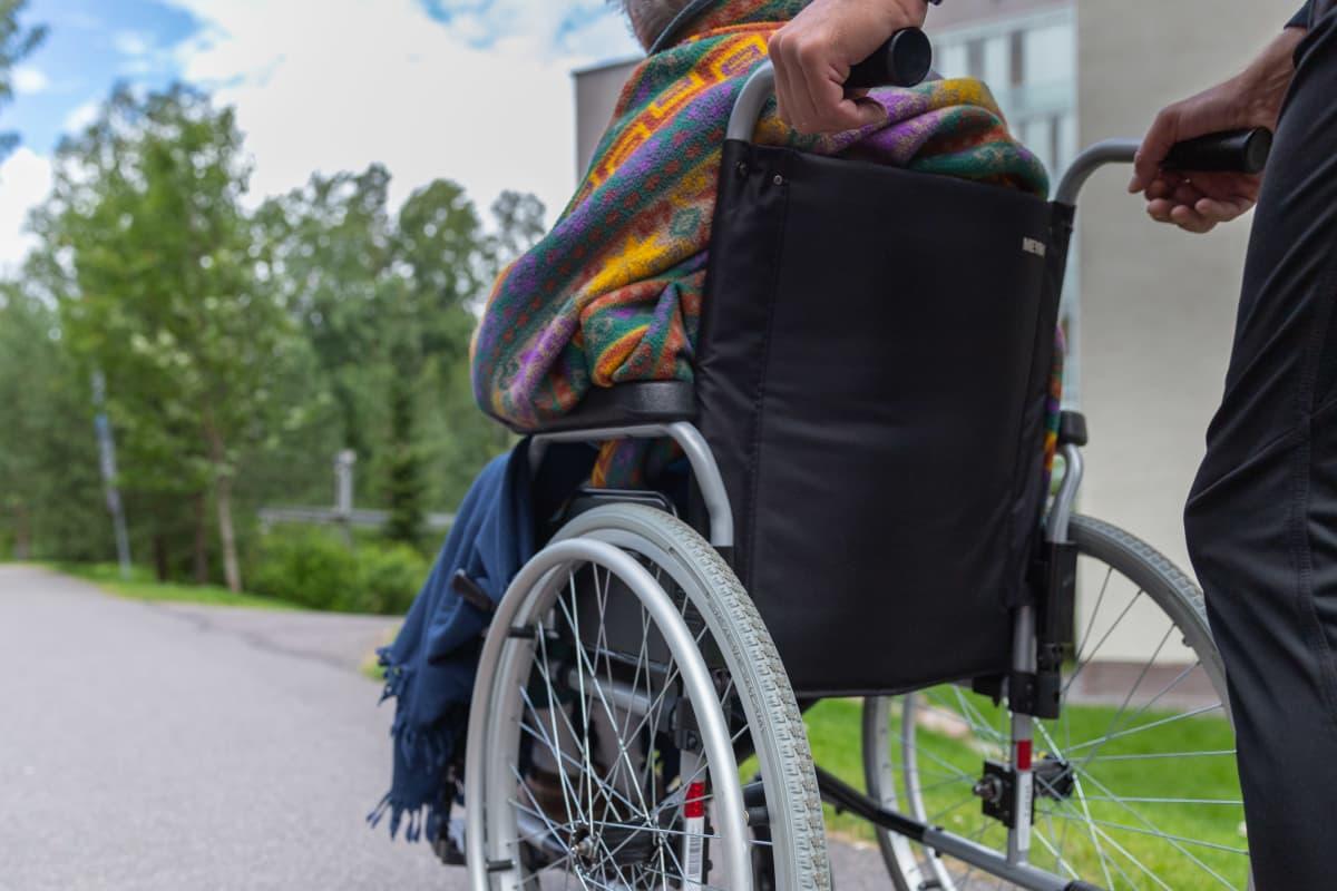 Vanhusta kuljetetaan pyörätuolissa.