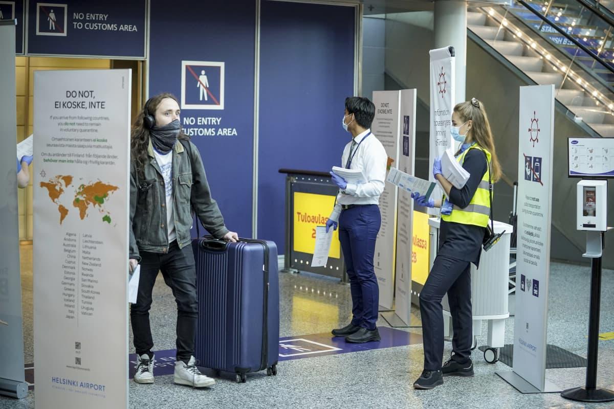 Matkustaja saapuu Helsinki-Vantaan lentoasemalle 7. elokuuta 2020. Häntä vastassa on kaksi henkilöä, joilla on ohjelehtinen Suomeen ulkomailta saapuville.