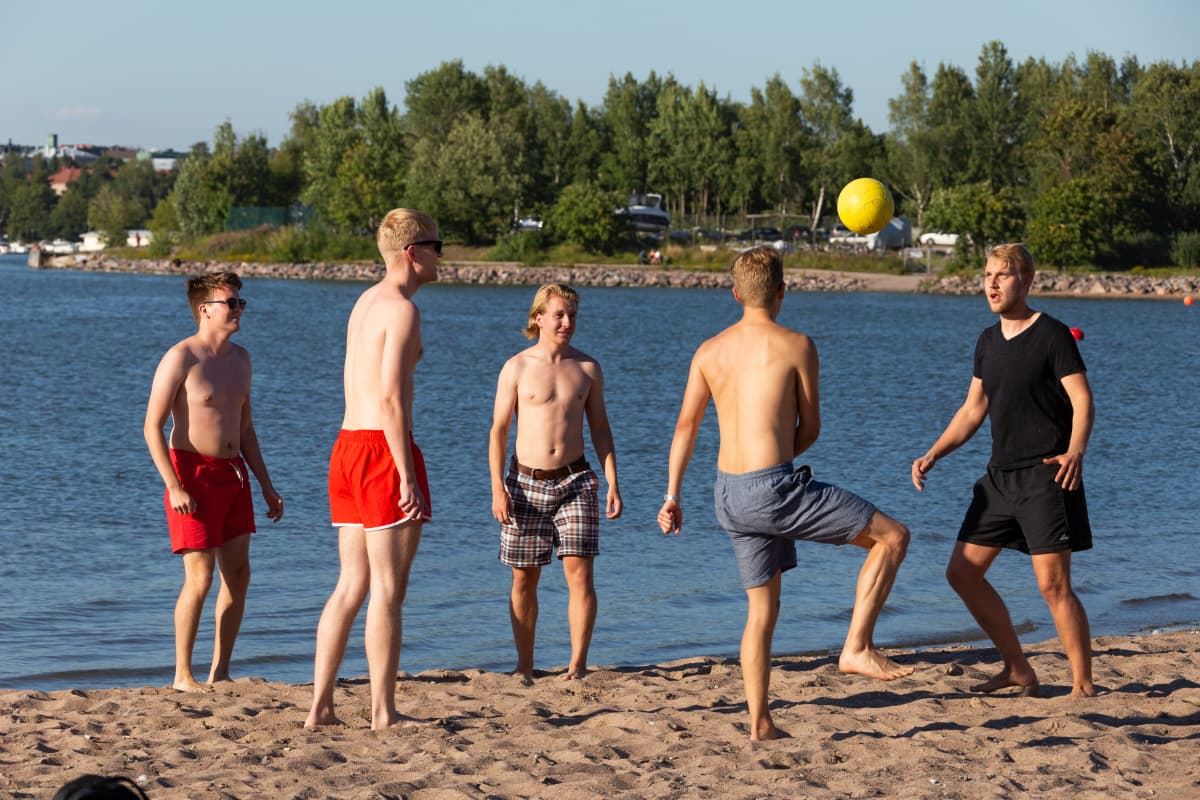 Miehiä pelailemassa palloa Hietaniemen uimarannalla.