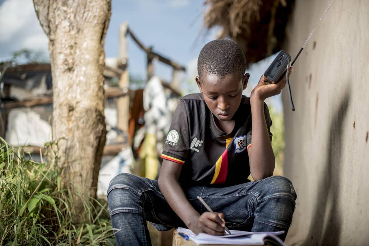 Ugandalainen poika opiskelee radion välityksellä.